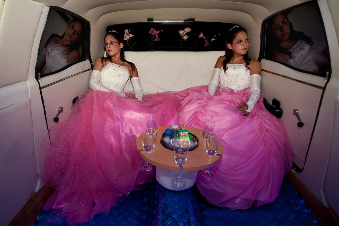 """The twins Laura and Belén on the day of their birthday celebration.In Latin America, the celebration of the fifteenth birthday of a teenager is very important because it marks the transition from childhood to maturity. Buenos Aires, Argentina, 2011. A luxury emblem used to transport politicians and rock stars in the '80s, nowadays the limousine turned into an icon of the Argentinean popular culture.  Brides in their white dresses, starlets television, fifteen years old celebrating their birthdays, and future husbands: they all share the  same sensation of sitting one night on an electric blue  Ford Fairlane from 1972. """"Limousine porteña,"""" explores a limited space in which many diverse things can happen. Between drunken, striptease, tears and laughter, the limousine is transformed into the scenario of ordinary people that use the dark tinted windows to release their fantasies and their transgression, under the curiosity of passersby. Buenos Aires, Argentina, 2011."""