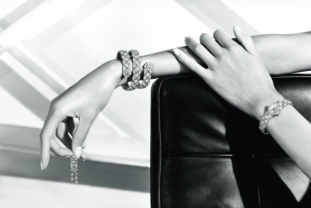 """Bracelet """"Signature Duo"""" en or blanc 18K serti de 2 diamants taille brillant pour un poids total de 2 carats et de 1178 diamants taille brillant pour un poids total de 26,6 carats. Boucles d'oreilles """"Signature White Tie"""" en or blanc 18K serti de 2 diamants taille coussin pour un poids total de 1 carat et 116 diamants taille brillant pour un poids total de 3,3 carats. Montre """"Signature White Tie"""" en or blanc 18K serti de 301 diamants taille brillant pour un poids total de 7,7 carats et nacre sculptée. Photo par CHANEL Joaillerie"""