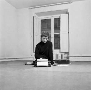 Paris, le 18 février 1956, portrait de l'écrivain Françoise SAGAN dans son appartement de la rue de Grenelle. Elle pose le dos tourné à la fenêtre, assise à même le sol, tapant un texte à la machine