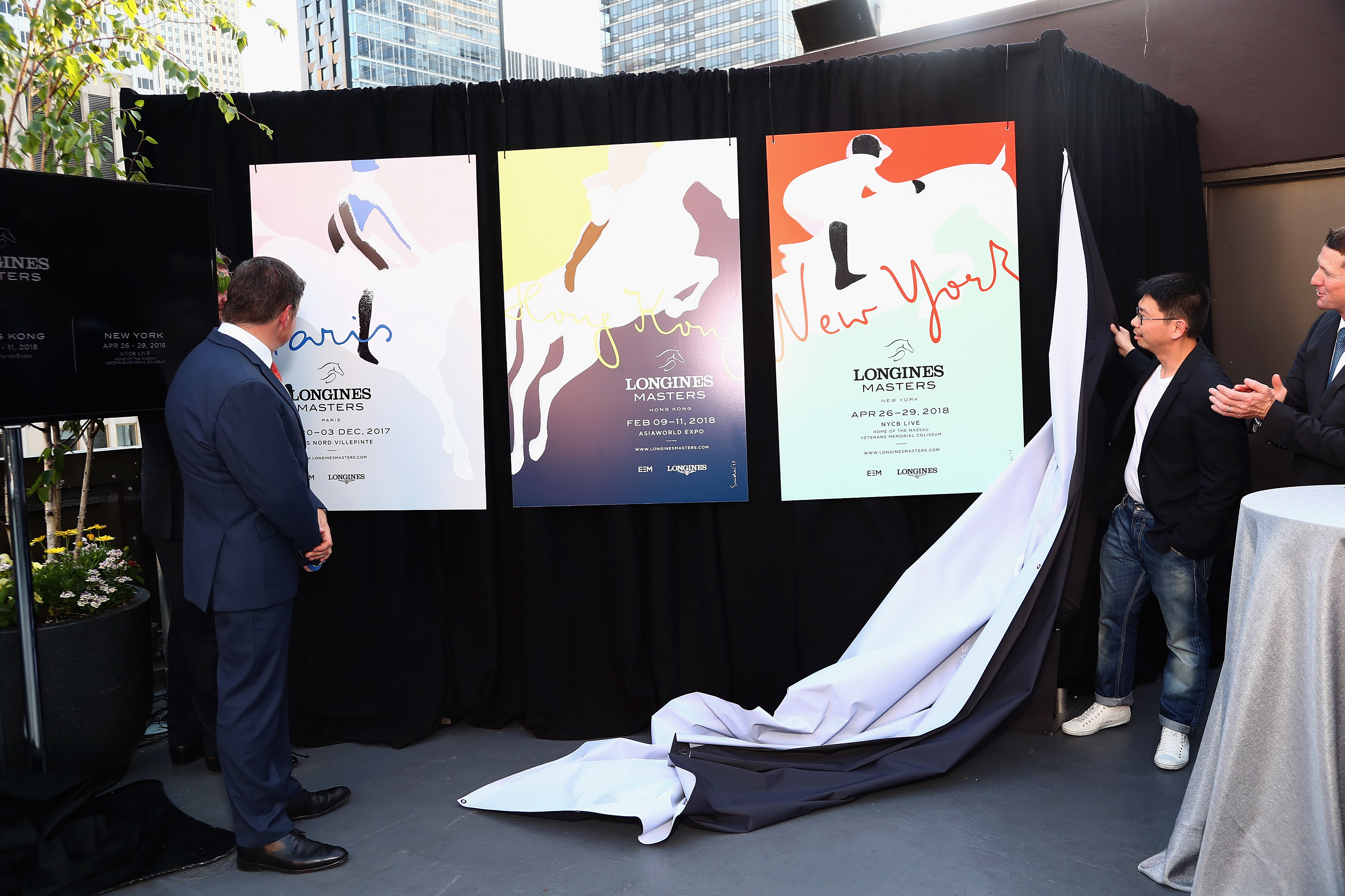 NEW YORK, NY - MAY 17: Artist Sirichai (R) reveals posters at the Longines Masters launch party celebrating Series' epic move to New York at Salon de Ning on May 17, 2017 in New York City. (Photo by Astrid Stawiarz/Getty Images for Longines)