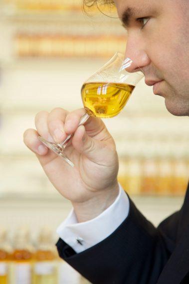 Photographie couleur de Renaud Fillioux de Gironde, nouveau Maître Assembleur à la tête du Comité de Dégustation Hennessy, dégustant une eau-de-vie dans le Grand Bureau.