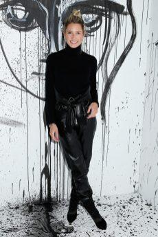 Helena Bordon portait une combinaison en cuir noir Dior et un pull col roulé en laine noire Dior.