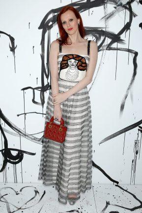 Karen Elson portait une robe bustier en tulle écru brodé Dior. Elle portait également des souliers Dior et un mini sac « Lady Dior ».