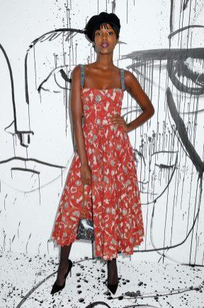 Leila Nda portait une robe en coton rouge imprimé Dior. Elle portait également des souliers Dior et un sac « C'est Dior ».