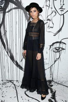 Olivia Culpo portait une robe en dentelle et soie noires Dior. Elle portait également un chapeau Dior, des boucles d'oreilles Dior, des souliers Dior et le sac « Le Cœur de Dior ».