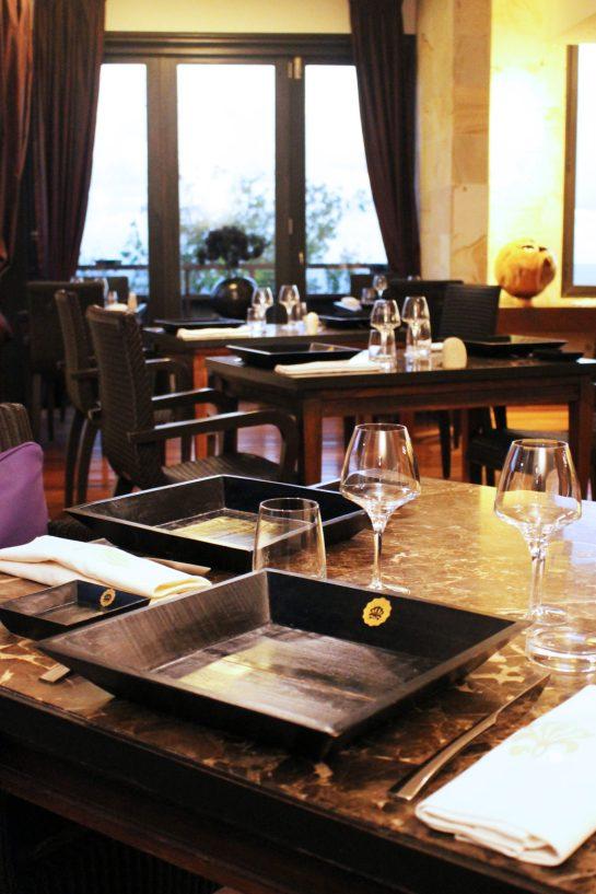 Assiettes de bois noir, décoration élégante et vue sublime sur l'océan indien : la salle du restaurant LE MAKASSAR