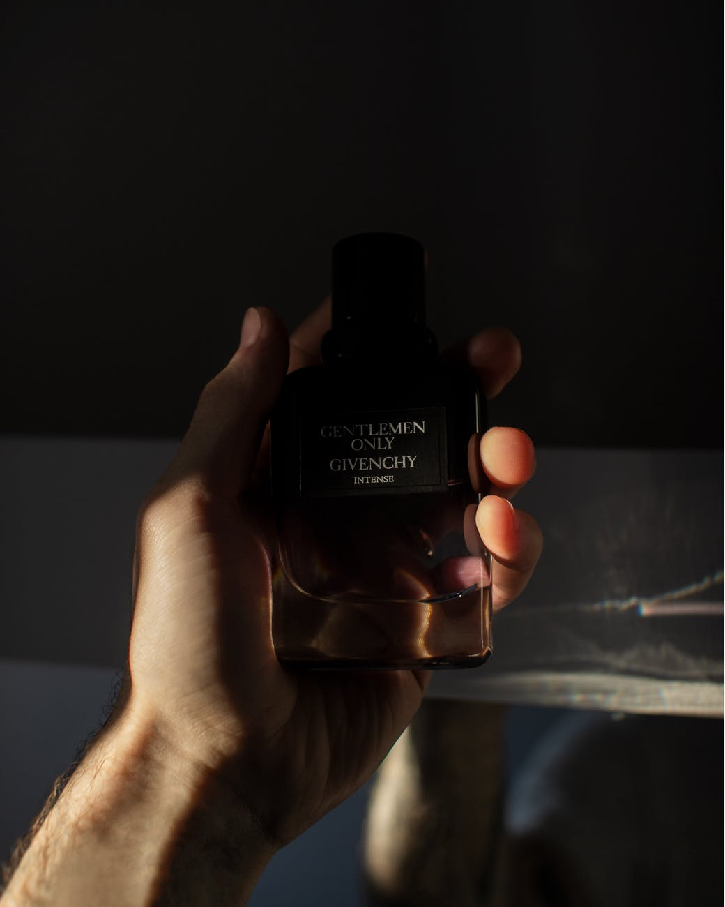 photo of person holding a gentlemen only cologne bottle by givenchy