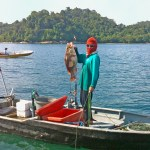 A local fisherman shows us his prize catch on the way to the floating fish farm