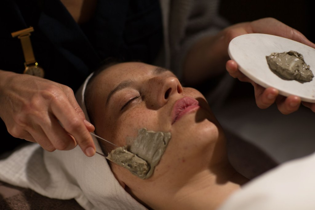 Woman having mud smeared on her face during one of the beauty treatments