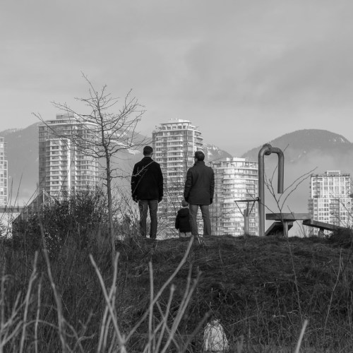 Two men view downtown Vancouver from an urban park. Canada