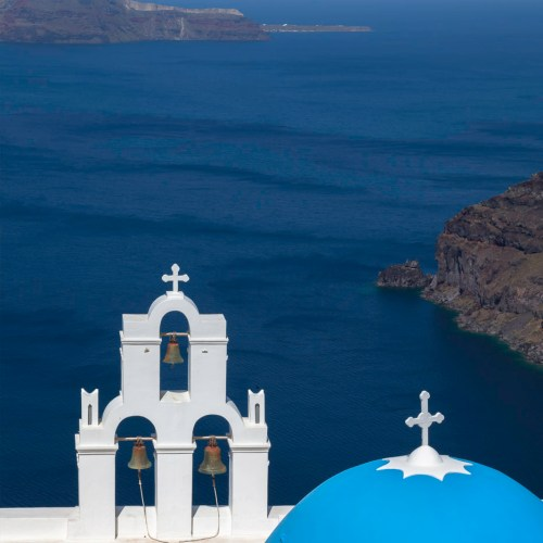 Sky blue domed church with bell tower above the caldera in Fira on the island of Santorini, Cyclades, Greece.