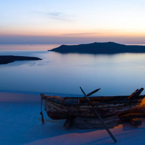 An old row boat on a Fira rooftop with sun setting over the caldera. Island of Santorini, Cyclades, Greece.