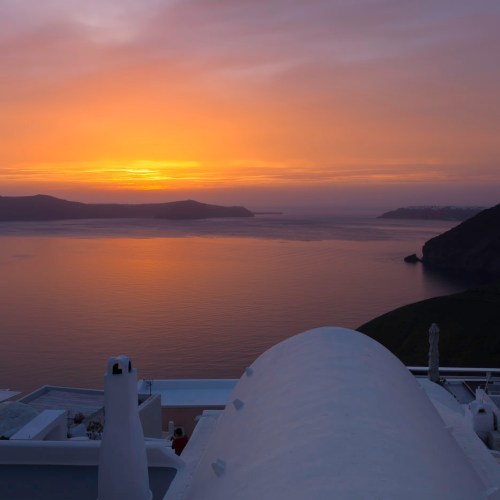 Sunset over the caldera in town of Fira on the island of Santorini, Cyclades, Greece.