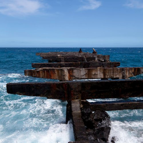 Dilapidated remains of a pier battered by ocean waves. Whittington Beach Park, Hawaii, USA.