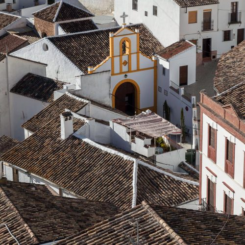 Roofs of homes and church of Setenil de las Bodegas, a town famous for its dwellings built into rock overhangs above the Rio Trejo. Province of Cádiz, Spain.