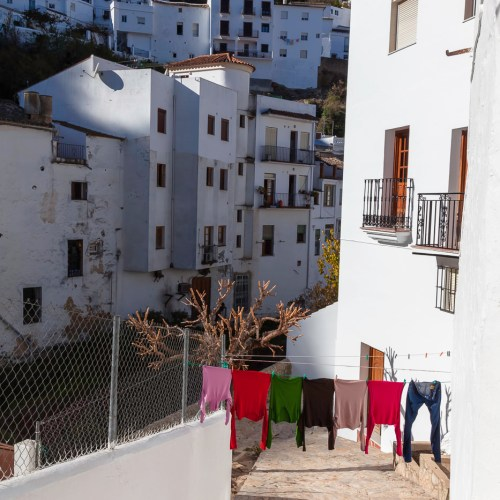 Laundry hanging across the street of the town of Setenil de las Bodegas, famous for its dwellings built into rock overhangs above the Rio Trejo. Cádiz, Spain.