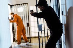prison guard aiming gun at escaping prisoner