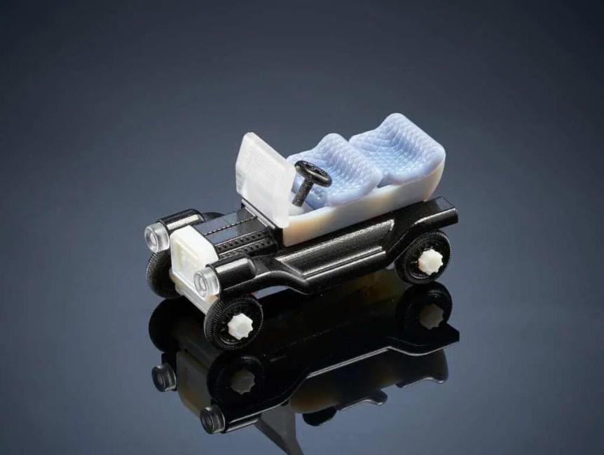 Carrinho de brinquedo impresso em impressora 3D. Carcaça na cor preta e bancos da na cor branca. Carro conversível. Modelo antigo.