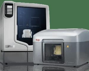 Dois modelos de impressoras 3D da Stratasys posicionadas uma ao lado da outra. Da esquerda para a direita, impressora com visor maior, possibilitando ver internamente a impressão do protótipo (impressora na cor cinza claro). Já a segunda modelo mais baixo com protótipo dentro da impressora nas cores cinza claro e escuro.