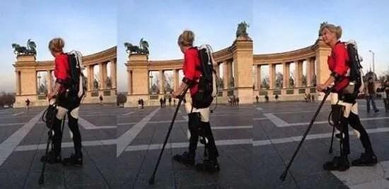 Amanda Boxtel utilizando Exoesqueleto criado a por empresas especialistas em impressão 3D. Amanda está usando camiseta vermelha e calça bege. Amanda está andando em praça pública, na Itália.