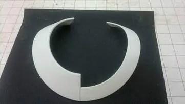 Acessório impresso em 3D na cor branca em cima de um suporte preto. Leia agora o nosso texto!