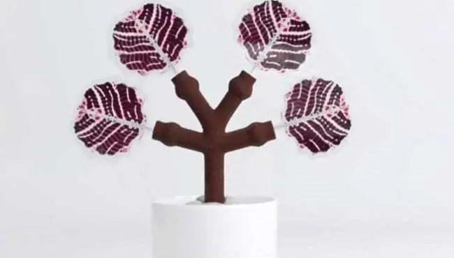 """Árvore com painel que capta energia solar em suas """"folhas"""" criada a partir de impressão 3D. Tronco marrom e folhas roxo com rosa."""