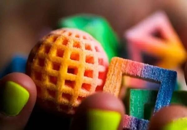Mulher segurando peças impressas em 3D pintadas de diferentes cores. Nestas peças, pode-se ver uma bola vazada e ao lado um cubo vazado, ambos coloridos.
