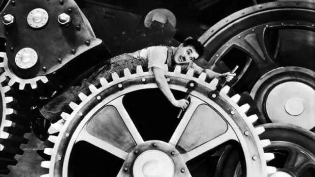 Cena do Filme Tempos Modernos, de Charles Chaplin. Ator deitado em engrenagem ajustando parafusos do maquinário.