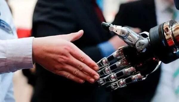 profissional da industria 4.0 com mão estendida para cumprimentar mão robótica.