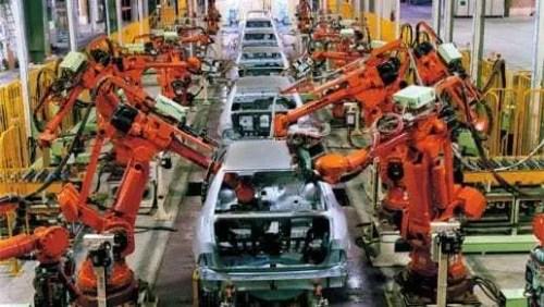 Linha de produção de indústria automotiva. Automóveis sendo feitos através de máquinas e não mais operários. Máquinas de cor laranja.