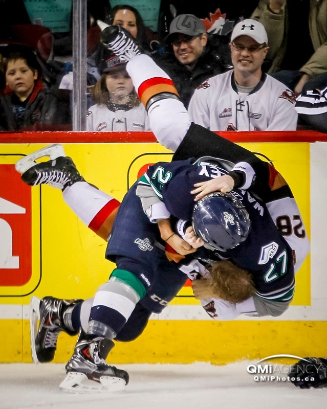 Evan Wardley of the Seattle Thunderbirds throws Elliott Peterson of the Calgary Hitmen to the ice in a scrap during WHL action in Calgary, Alta. on Sunday January 5, 2014. The Hitmen won 10-2.
