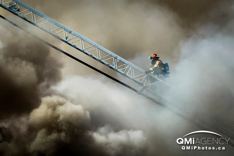 A firefighter climbs through a cloud of dense smoke at Southampton Green Condominium Complex next to Elbow Drive north of Anderson Road SW in Calgary, Alta. on Wednesday, Aug. 14, 2013. Alvin Bali, a third-floor resident who claims to have called 911, says there were no sprinklers in the building and he never heard an alarm.