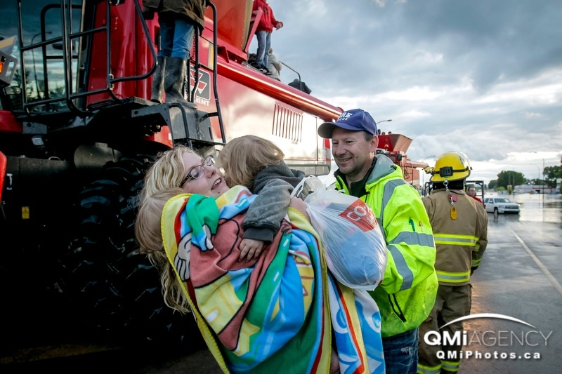 Mom Lynette is reunited with her kids Indyana, 2, and Gunnar, 1, after being helped down from a combine by firefighter Murray Muise in High River, Alta. on Thursday, June 20, 2013. The Highwood River running through High River was flooding extremely, prompting a town wide evacuation.