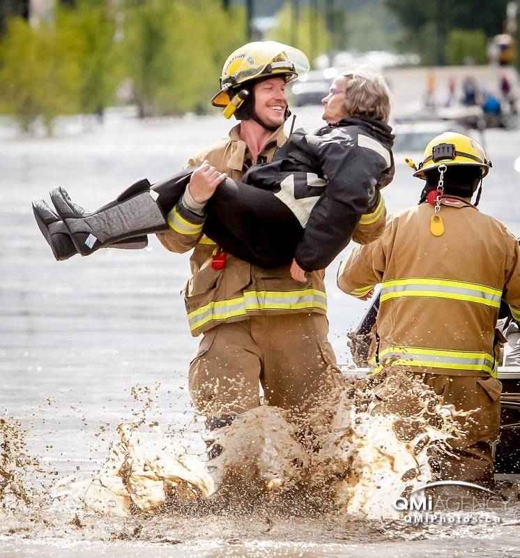 Volunteer firefighter Shawn Wiebe carries flood evacuee Sheila Rowland to dry land from the boat in which she was rescued in High River, Alta. on Thursday, June 20, 2013. The Highwood River running through High River was flooding extremely, prompting a town-wide evacuation.