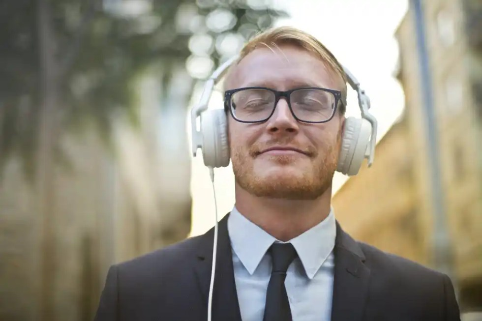 cheerful man in formal wear enjoying music