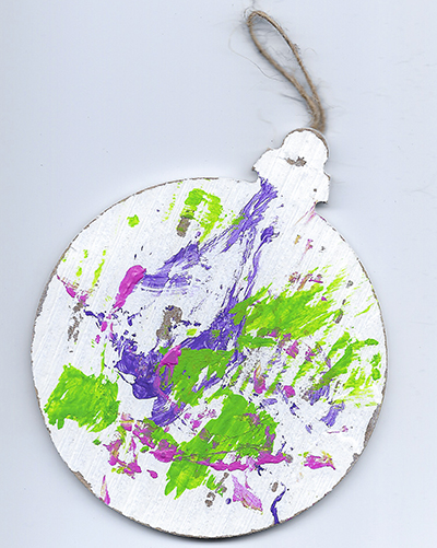 An abstract acrylic painting on a wooden ornament with purple, green, and pink streaks and dots