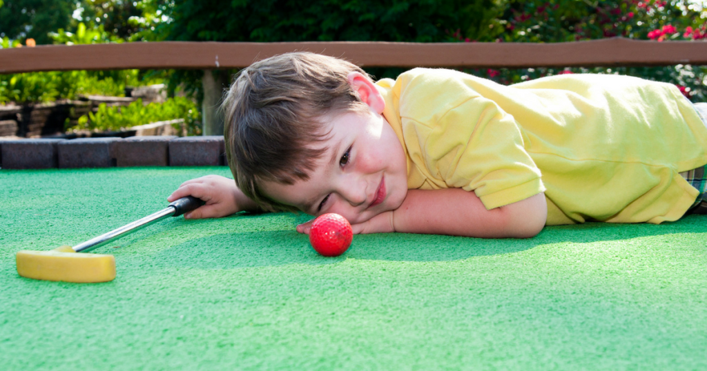 Little boy playing mini-golf