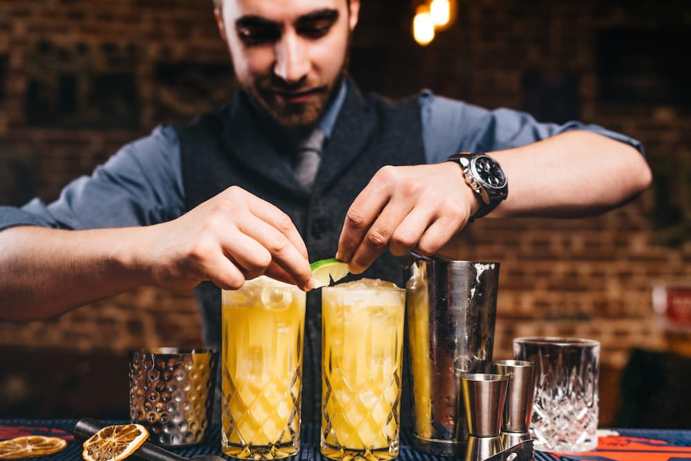 Professional bartender garnishing with lime cocktails