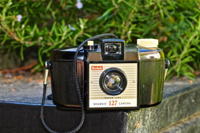 "This is the second version, with vertical ribbing on the body, and a larger viewfinder and larger lens (marked 'Dakon'). The curved rear side of the camera was not just a design affectation; it had a proper purpose: the very simple cheap curved plastic lens on the front wasn't corrected to give a ""flat field"" result on flat film, so the centre of the image was fairly sharp, but the edges would have been blurred and unfocused if <i>the film itself</i> hadn't also been curved, following the guides inside the curved back of the camera! I didn't know that at the time, but was just so taken with the bowl-like shape of this simple, elegant form-follows-function black-body-white-buttons plastic Brownie"