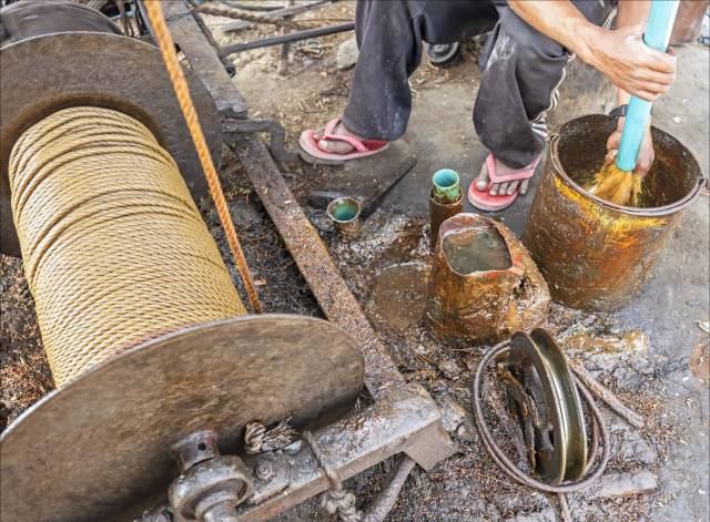 Emptying the oil from the pipe into a jerry can