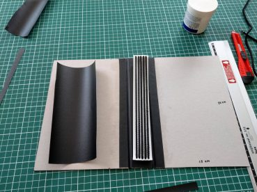 cut a strip of styrene, narrower than the spine, drill holes in it and thread cloth covered elastic through it