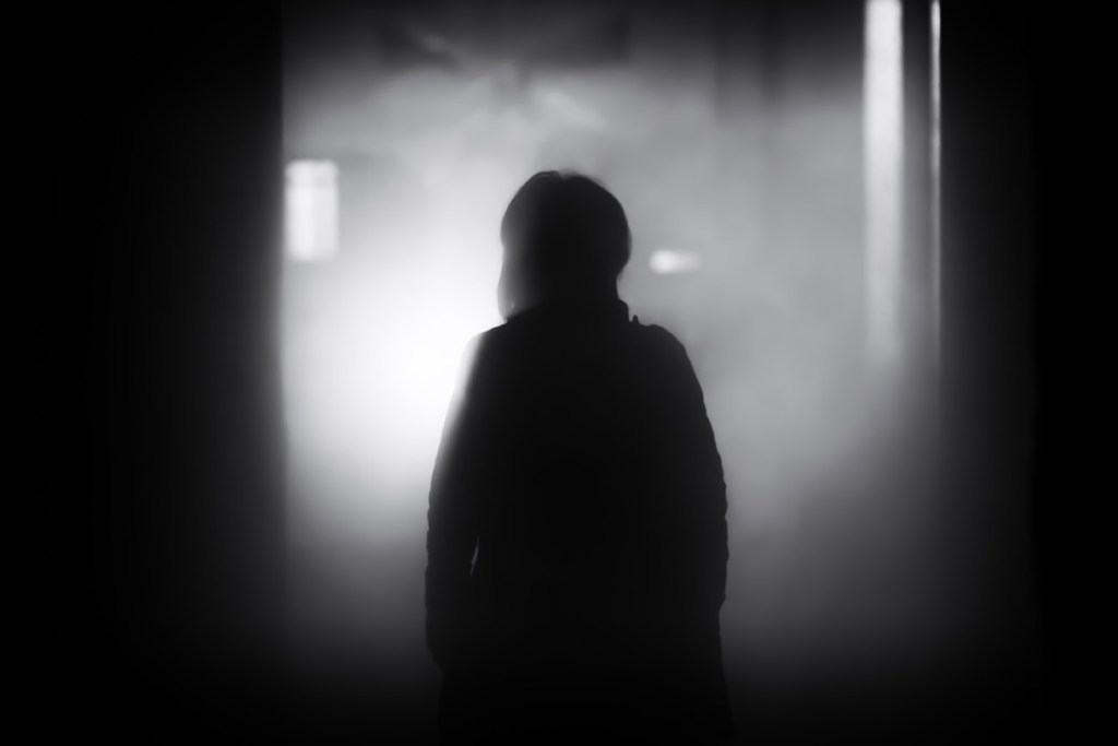 Mysterious silhouetted figure in a foggy indistinct gray setting