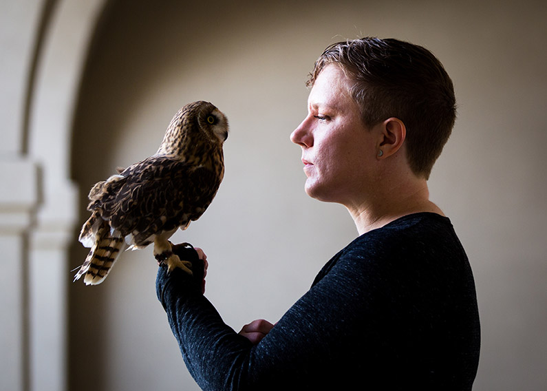 The author, under moody lighting, holding an owl