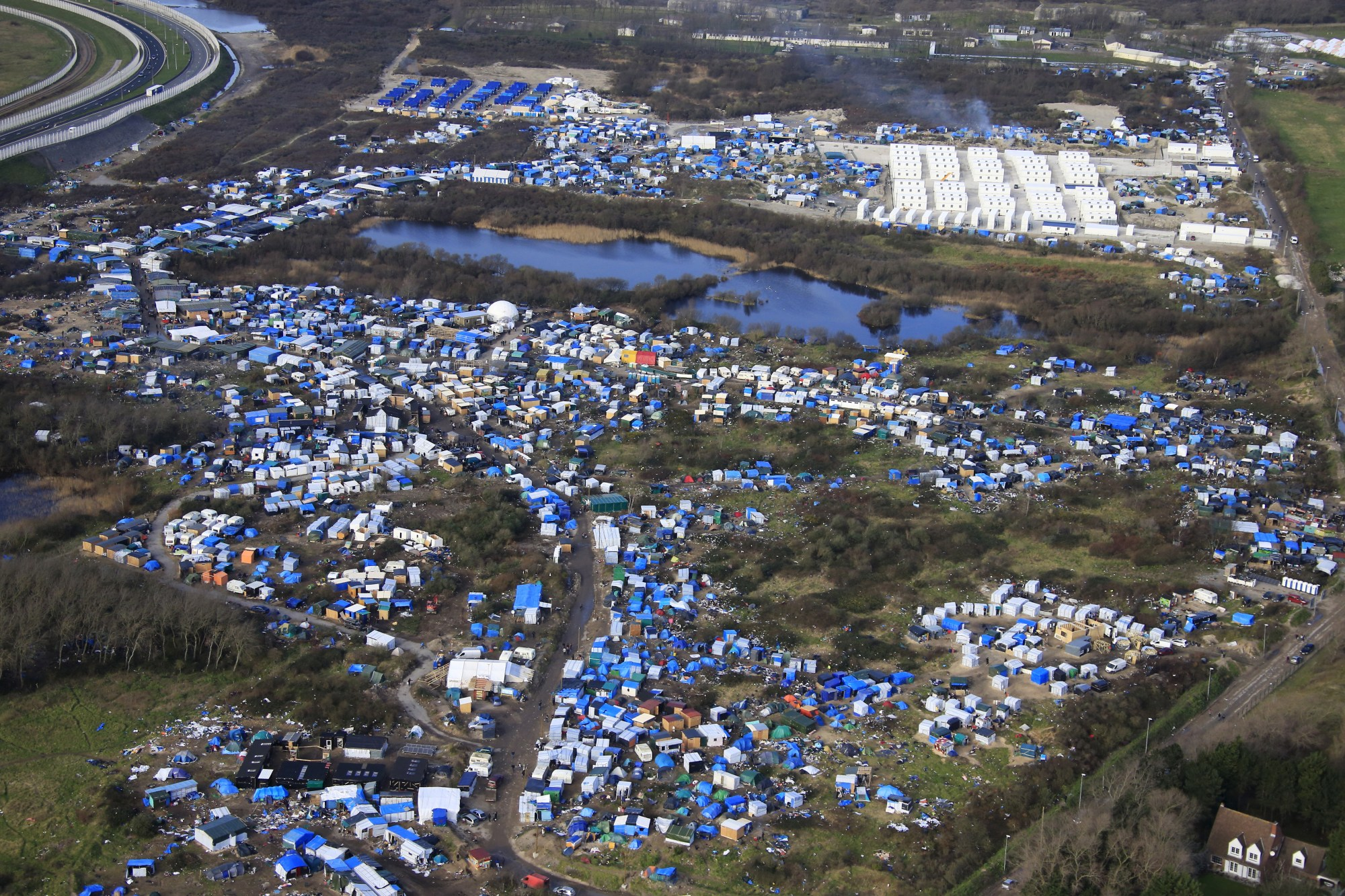 hight resolution of aerial view of a makeshift camp as containers rear are put into place to