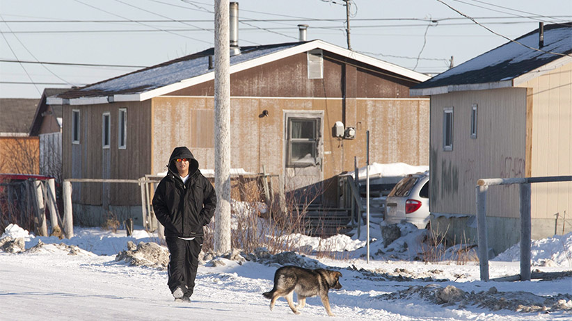 A man walks down the street in Attawapiskat, Ont., Tuesday November 29, 2011. (Adrian Wyld/CP)
