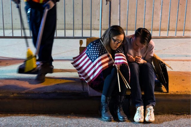 People sit outside the Jacob Javits Center waiting for election results following a rally for Democratic presidential candidate Hillary Clinton in New York Wednesday, Nov. 9, 2016. (AP Photo/Craig Ruttle)