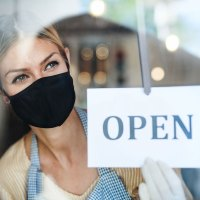 woman wearing covid mask with open sign on window