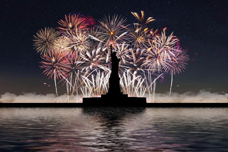 Fireworks light the sky behind the statue of liberty