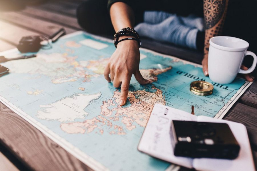 Traveller plans their adventure in front of a world map