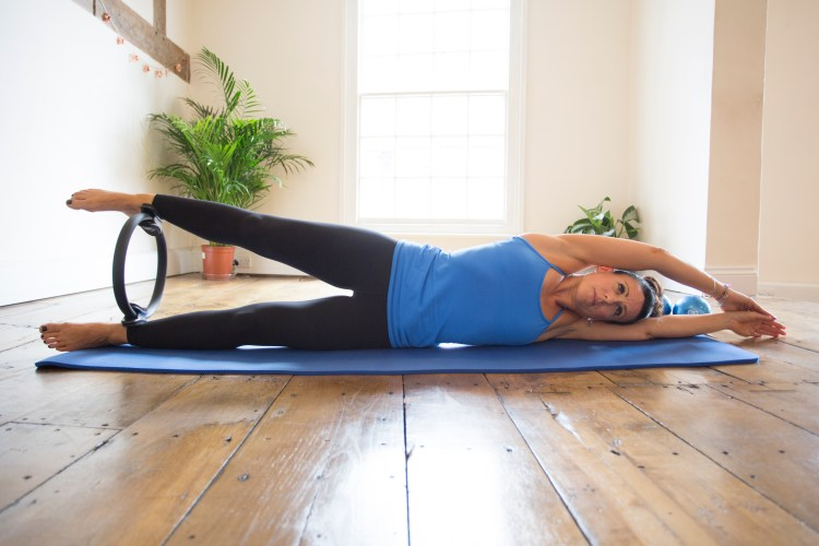 Model with Pilates ring lying on Pilates mat by Pilates-Mad